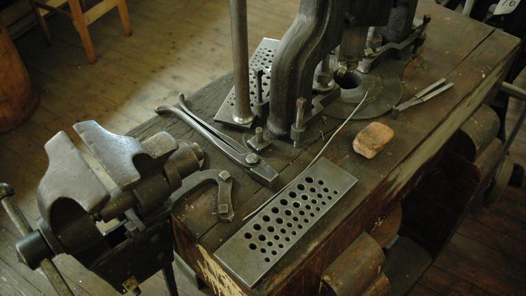 Vue de quelques outils de bijouterie. Filière à profil rond, étau et presse manuelle. Photo © Arnaud Sprimont.