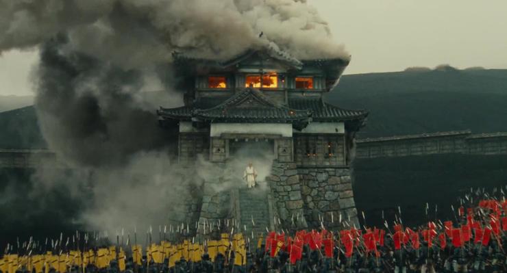 Le vieil homme sort de sa forteresse en flamme, entouré d'un tourbillon de fumé ; il est gris, il semble déjà mort, plus proche de l'esprit que de l'être humain.